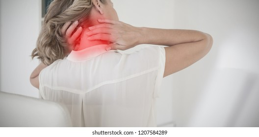 Casual businesswoman rubbing her neck against highlighted pain