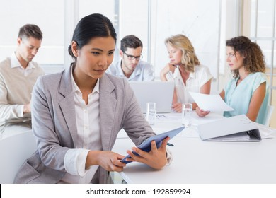 Casual businesswoman using her tablet during a meeting in the office
