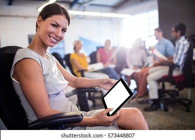 Casual businesswoman using a tablet during a meeting