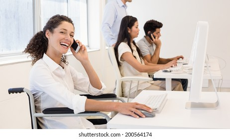 Casual businesswoman in wheelchair on the phone smiling at camera in the office
