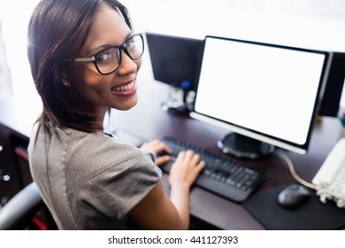 Casual businesswoman working on laptop at office