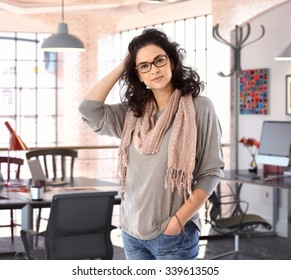 Casual caucasian attractive fashion designer woman standing at business studio office. Wearing glasses, hand in pocket, looking at camera.