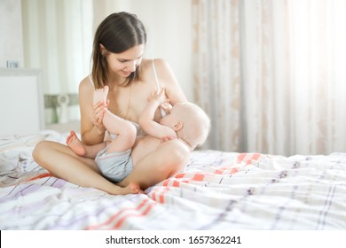 Casual Caucasian mother with baby on the bed, mother breastfeeds the baby. Pillow on hand for feeding. The concept of breastfeeding and motherhood