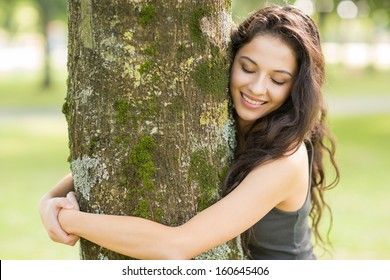 Casual cheerful brunette embracing a tree with closed eyes in a park on a sunny day
