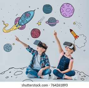 casual children using virtual reality headsets while sitting on the floor with doodle space pictures on walls
