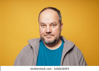 casual chubby confident mature man against yellow background with copy space