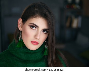 Casual close up portrait of happy young brunette woman with trendy makeup green sweater and custom brush earrings.