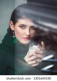 Casual close up portrait of happy young brunette woman with trendy makeup green sweater and custom brush earrings holding latte cup looking trough cozy cafe window with reflections.