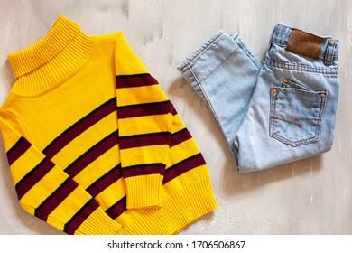 明るい背景に少年用のカジュアルな服。青いジーンズと黄色いセーターのトップビュー。