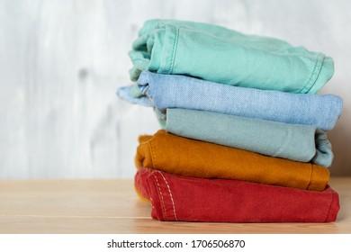 明るい背景に少年用のカジュアルな服。積み重ねた色のジーンズ。