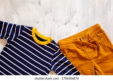 Casual clothes for a boy on a light background. Colored jeans and a t-shirt with a long sleeve top view.