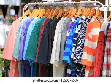 Casual clothes hang on clothes rack for sale.