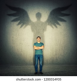 Casual confident man arms crossed. Full length portrait casting a superhero shadow with angel wings on a dark room wall. Inner power, ambition and leadership concept.