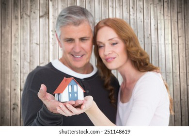 Casual couple holding small house against wooden planks background
