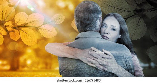 Casual couple hugging each other against autumn scene