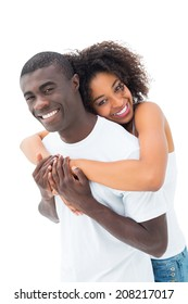 Casual couple hugging and smiling at camera on white background