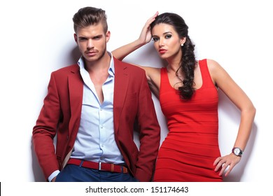 casual couple looking at the camera while leaning on a white wall