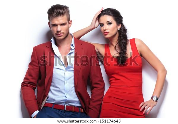 lässiges Paar, das die Kamera anschaut und sich auf eine weiße Wand stützt