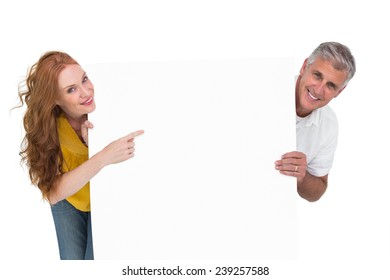 Casual couple showing a poster on white background