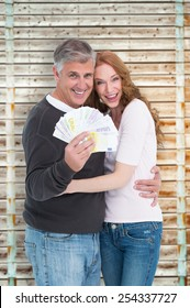 Casual couple showing their cash against wooden background in pale wood