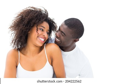 Casual couple smiling at each other on white background