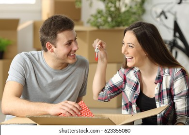 Casual couple unpacking belongings and showing keys sitting on the floor of the loving room in their new house with boxes in the background