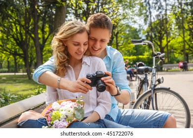 Casual couple using compact dslr photocamera in summer park.