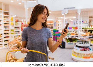 Casual cute female, using her mobile phone in modern market.