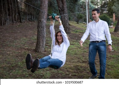 Casual dress couple plays in a zip line in the garden of their home