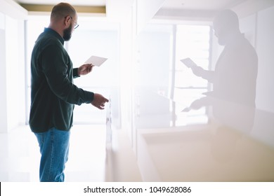 Casual dressed bearded man in eyewear reading letter with financial bills opening apartment.Hipster guy holding paper card with invitation standing in hallway.Male received receipt