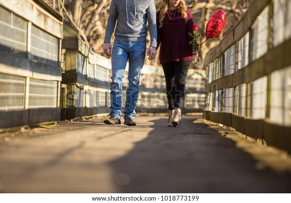 casual dressed couple walking toward viewer holding hands torso no eyes she id holding a red balloon and a red rose