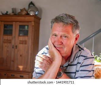 casual dressed happy man sitting at home at the table and smiles