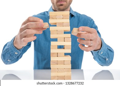casual dressed man playing a game of jenga, just removed simultaneously two bricks at a time