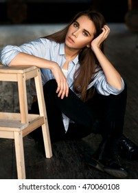 Casual dressed pensive girl sitting on a grunge floor near wood stool