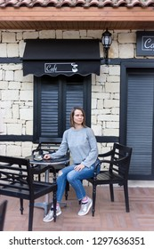 Casual dressed woman sitting in a cafe shop