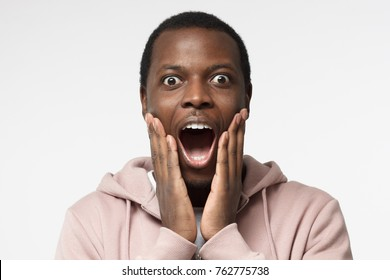 Casual dressed young african man in pink hoodie shouting oh my god with open mouth, surprised by low price and sales, isolated on gray background