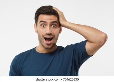 Casual dressed young man in blue t-shirt shouting oh my god with open mouth, surprised by low price and sales, isolated on gray background
