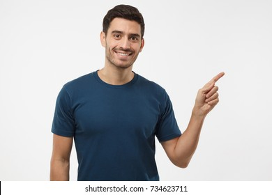 Casual dressed young man in blue t-shirt pointing right with his finger isolated on gray background