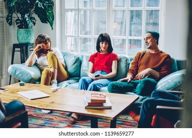 Casual dressed young people talking and spending leisure time together in modern flat with stylish interior.Hipster guys communicating with each other sitting on comfortable couch