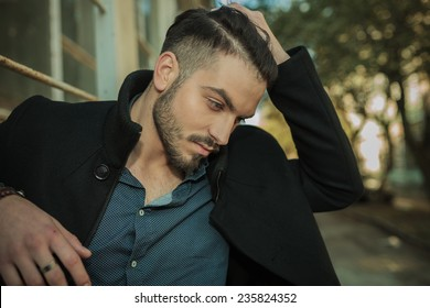Casual fashion man looking down while fixing his hair, close up picture.