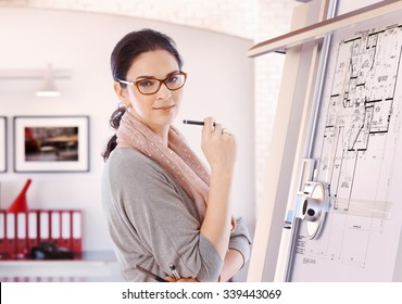 Casual female caucasian architect standing at drawing board and floor plan with pencil in hand at office. Wearing glasses, smiling, looking at camera.