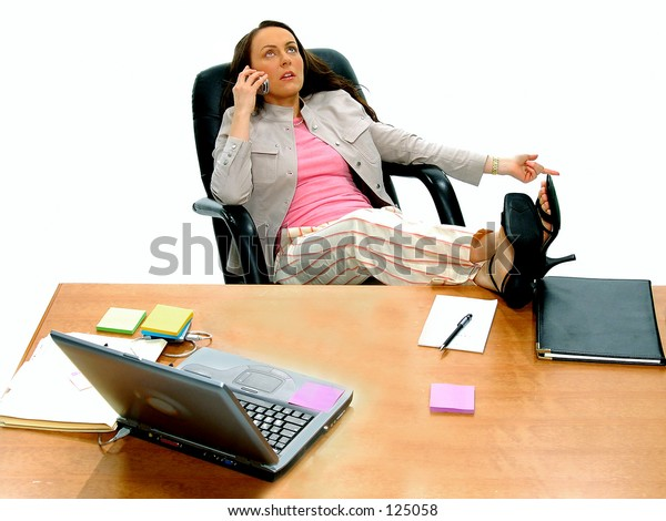 Casual female Executive kicked back at her desk talking on cell phone