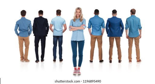 casual female leader stands on white background with arms crossed behind her team of men and smiles, full length picture