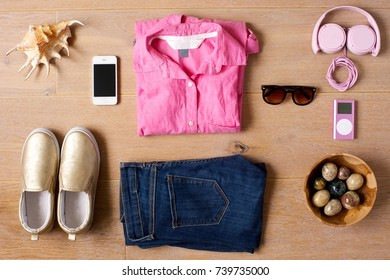 Casual female outfit laid out on a wooden background. Shoes, jeans, pink shirt, sunglasses, phone, pink music player and headphones. Sea shell and a bowl of colored stones a sidepieces.