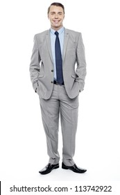 Casual full length portrait of professional businessman. Standing with hands in trousers pocket
