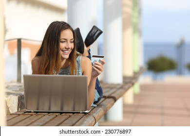 Casual girl buying online with a laptop and paying with a credit card lying on a bench outdoors in the street
