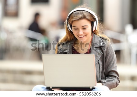 Casual girl listening music with headphones and searching songs in a laptop sitting on a bench in the street