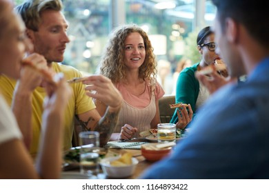 Casual girl with wavy hair eating pizza and looking at one of her friends during talk by dinner