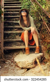 Casual girl wearing long orange skirt sitting on the old wooden stairs outdoor.