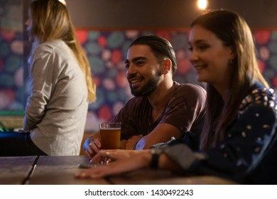 Casual guy having a beer in a bar in latino america smiling and having fun.